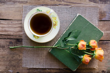 Black Tea In China Teacup On A Hessian And Wood Background, With Fresh Orange Roses