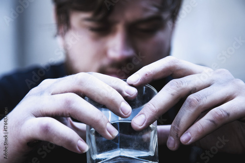 Close up of man holding a glass of vodka. Drunk young people. (alcoholism, pain, pity, hopelessness, social problem of dependence concept)
