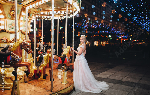 Foto op Plexiglas Las Vegas The bride blond in a light pink wedding dress is standing near the carousel in the background of a night cityscape .