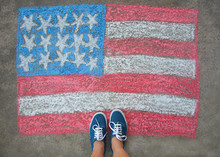 Feet In Blue Sneakers Standing Above A Chalk Drawn American Flag