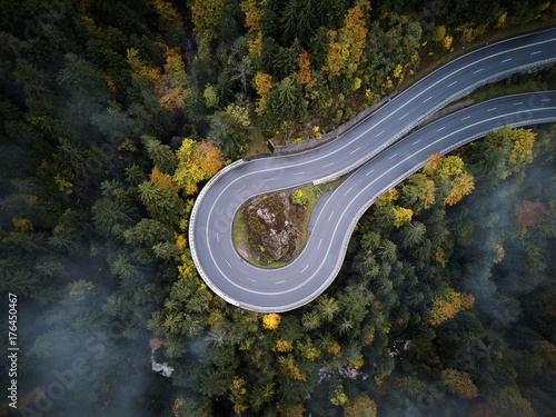 Deurstickers Luchtfoto street from above trough a misty forest at autumn, aerial view flying through the clouds with fog and trees