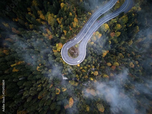 Garden Poster Air photo street from above trough a misty forest at autumn, aerial view flying through the clouds with fog and trees