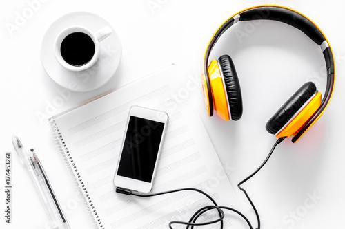 Fototapeta Worktable of composer today. Headphones, phone, music notes on white background top view obraz na płótnie