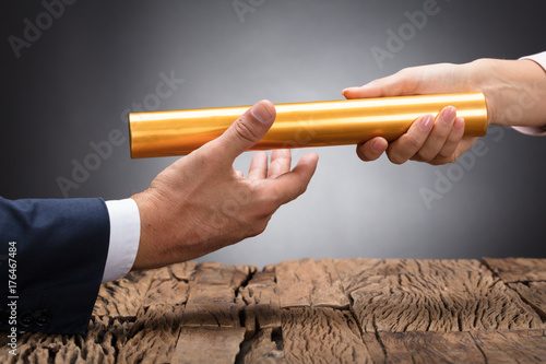 Cuadros en Lienzo  Close-up Of A Businessperson Passing Baton