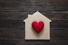Home Symbol With Red Heart Shape On Wooden Background.