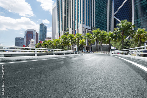 Fototapeta pusta asfaltowa droga z nowoczesnymi budynkami