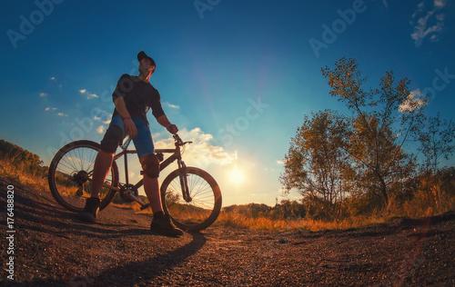 Fototapeta Młody kaukaski atletyczny facet w poduszkach na kolana polega na rowerze sportowym