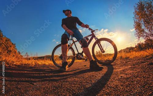 Fototapeta Kaukaski atletyczny facet w ochraniaczach na kolana polega na rowerze sportowym