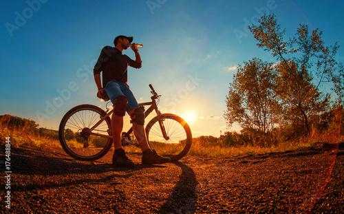 Fototapeta mężczyzna w czarnej koszulce, spodenkach z niebieskimi spodenkami i nakolannikach na rowerze sportowym