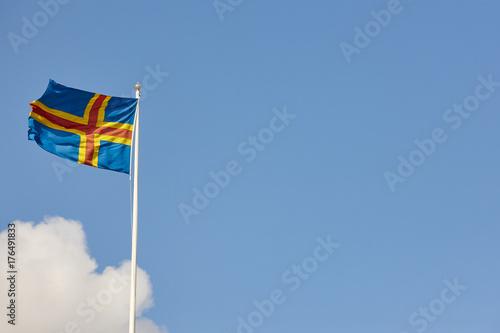 Plakat Flaga Wysp Alandzkich nad błękitne niebo. Finlandia tło.