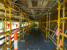A Footpath Running Through Scaffolding Underneath A Bridge.