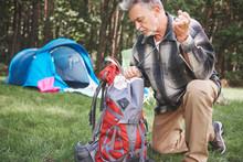 Senior Man Beside Tent, Packin...