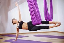 Young Beautiful Yogi Woman Doing Aerial Yoga Practice In Purple Hammock In Fitness Club.