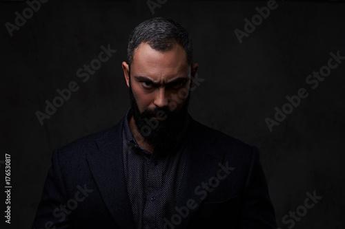 Fototapeta  Serious, bearded male dressed in a grey suit.