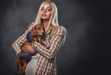 A Stylish Blonde Female Holds ...