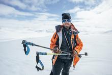 Portrait Of Happy Skier With Ski Pole