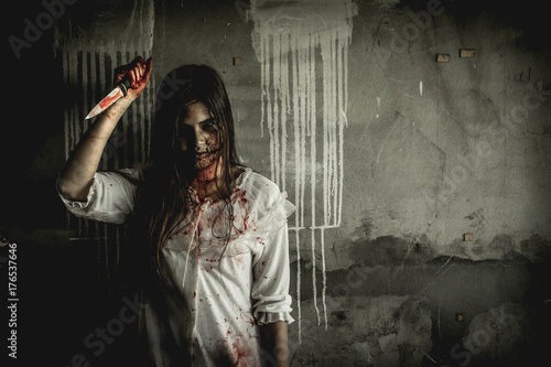 Fotografie, Tablou Asian girl dress killer to Halloween festival She's holding a kitchen knife and a big soaked with blood with terrible eyes ready to kill people