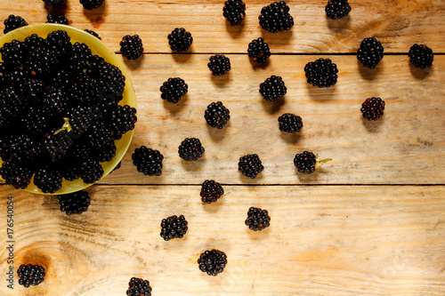 Valokuva  Ripe blackberries in a basket on a rustic wooden table.