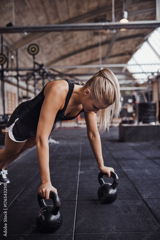Fényképezés  Young woman working out with weights on a gym floor