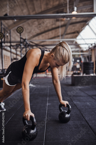 Vászonkép  Young woman working out with weights on a gym floor