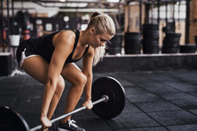 Focused Young Woman Lifting Heavy Weights Alone In A Gym