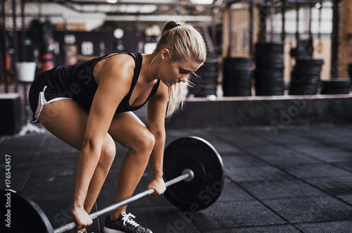 Vászonkép  Focused young woman lifting heavy weights alone in a gym