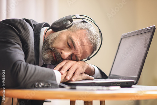 Fényképezés Senior business man sleeping on his laptop with his headphones on, listening to