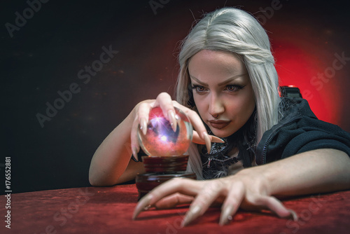Fotografie, Obraz  Young witch with silver hair casting a spell, invoking spirits and being possess