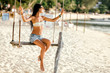 Woman Sitting on a Swing at the Beach
