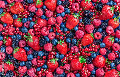Berries overhead large closeup colorful assorted mix of strawbwerry, blueberry, raspberry, blackberry, red currant in studio on dark background in studio