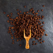 Coffee beans in a wooden scoop on slate plate background