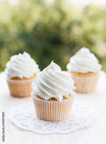 Photo  Vanilla cupcakes topped with swirl of sweet vanilla frosting captured on the wooden table in a sunny day