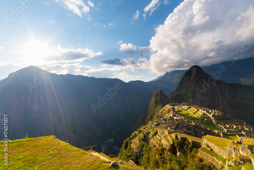 Recess Fitting Ruins Machu Picchu illuminated by the warm sunset light. Wide angle view from the terraces above with scenic sky and sun burst. Dreamlike travel destination, world wonder. Cusco Region, Peru.
