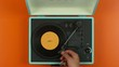 Overhead view hands closing lid on colorful vintage record player, slow motio