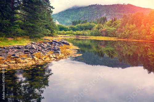Plakat Skalisty lakeshore spokojny halny jezioro w jesieni. Piękna przyroda Norwegii. Odbicie na wodzie