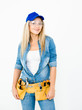 Beautiful young woman contractor with tool belt on white background