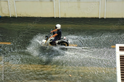 Plakat Mężczyzna jedzie motocykl na ulicznym powodzie. Nieostrość.