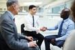 Two intercultural businessmen handshaking after seminar