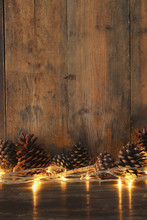 Holiday Image With Christmas Golden Garland Lights And Pine Cones Over Wooden Background
