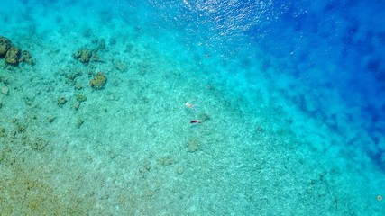 P02675 Aerial flying drone view of Maldives white sandy beach abstract waves water surface texture on sunny tropical paradise island with aqua blue sky sea ocean 4k
