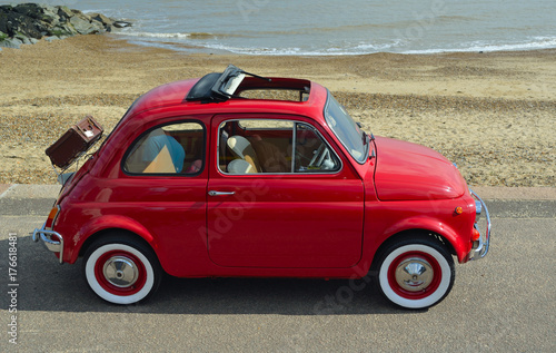 Fotografia  Classic Red Fiat 500  motor car with picnic basket parked on seafront promenade