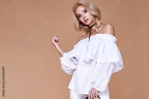 Photo Sexy beautiful pretty young woman long blond curly hair slinkybody shape natural organic make up wear fashion clothes silk blouse cotton trousers hold hand bag accessory jewelry model glamour style