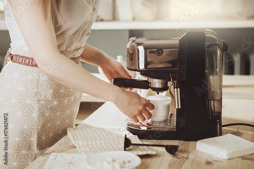 Woman making fresh espresso in coffee maker Fototapeta