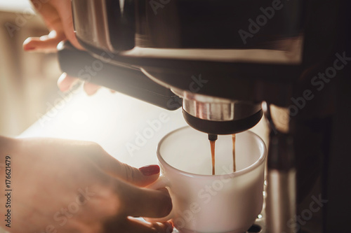 Valokuva Woman making fresh espresso in coffee maker