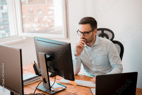Fototapety, obrazy: Man working on computer in modern office interior.