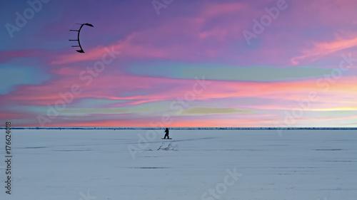 Plakat Kania surfingowiec na zamarzniętym jeziorze w wsi od holandii w zimie przy zmierzchem