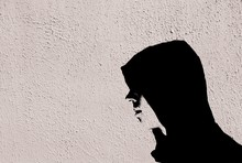 Young Teenage Bully Boy In Black Hoodie With Graffiti Stencil Effect On White Wall