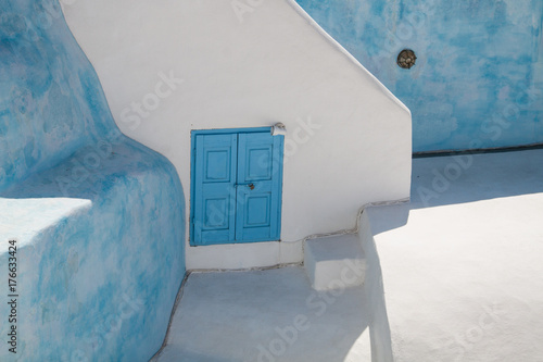 Fototapety, obrazy: Small blue window  with closed venetian blinds, on the background of white and blue wall, Santorini, Greece