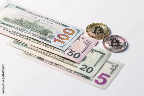 Photo  Gold and silver bitcoins around the banknotes of US dollars of different denominations