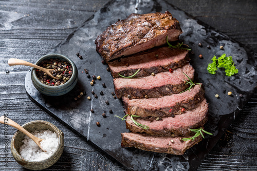 Sliced grilled roast beef with salt and pepper on marble plate on wooden old rustic table Black background Fototapeta